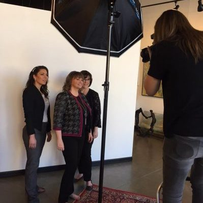 Dr. Harrison stands in front of a photographer posing with her team for a photo shoot  at Eva Reynolds Fine Art Gallery